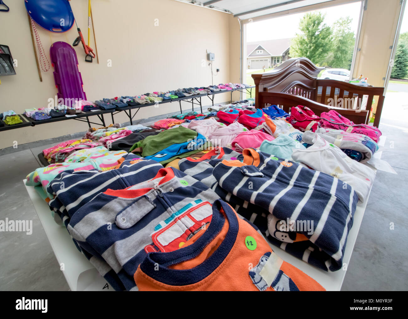 Tables full of dishes, toys, and children's clothing for sale at a typical American garage sale - Stock Image
