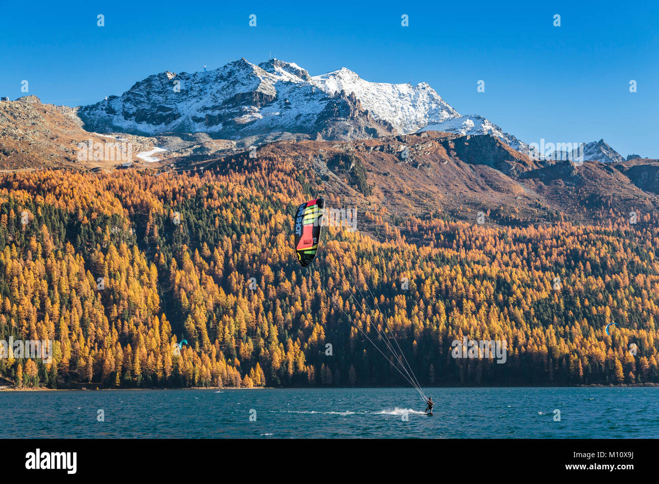 Wind surfing on Lake Silvaplana with fall foliage color in the larch trees in the Engadin Valley, Graubuden, Switzerland, - Stock Image