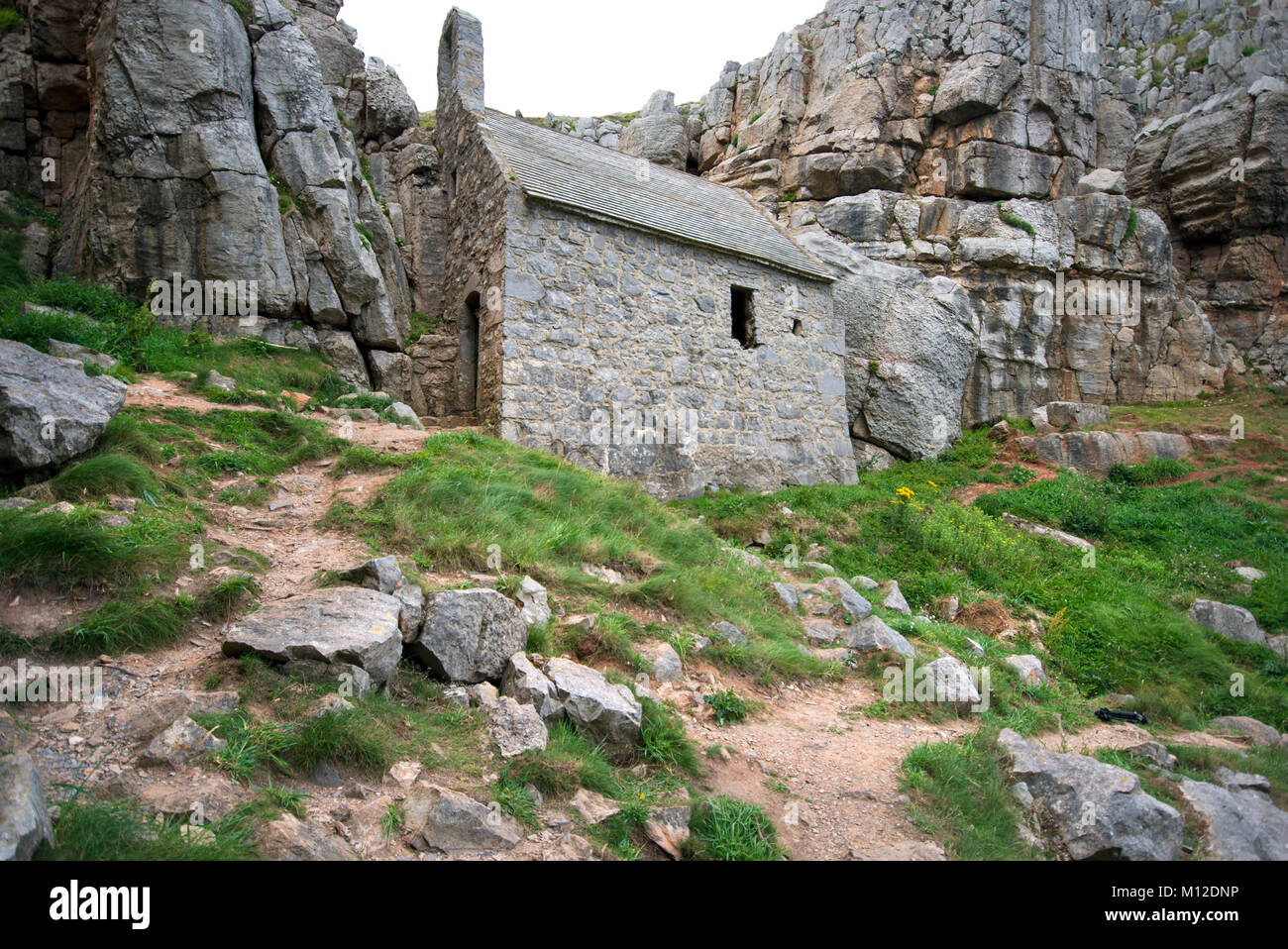 St Govan's Chapel tucked beneath the cliffs at St Govan's Head on the coast of Pembrokeshire in South Wales. - Stock Image