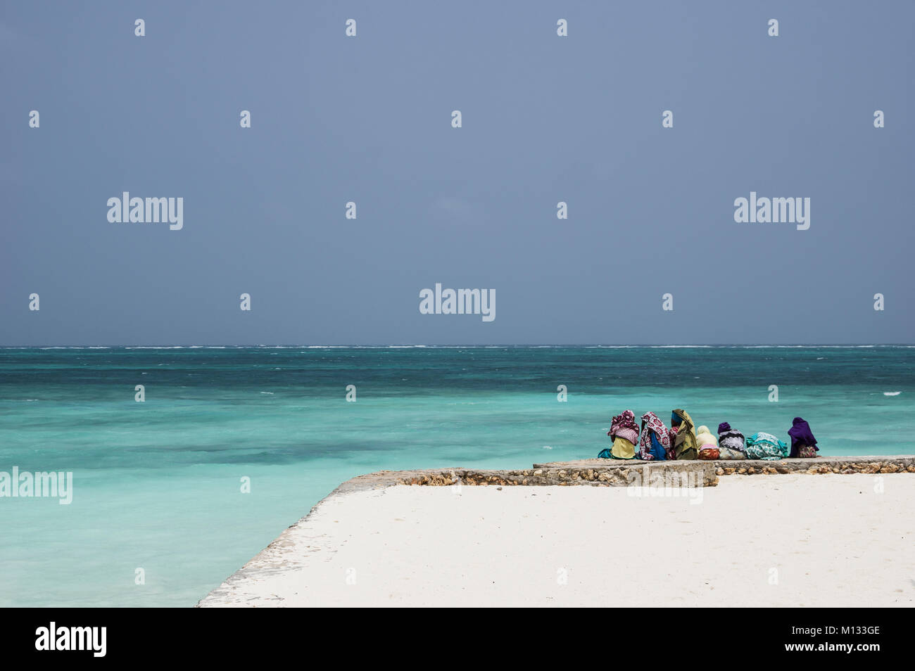 Local children in Nungwi, Zanzibar, Tanzania, sitting before the turquoise water of the Indian Ocean wearing Islamic - Stock Image