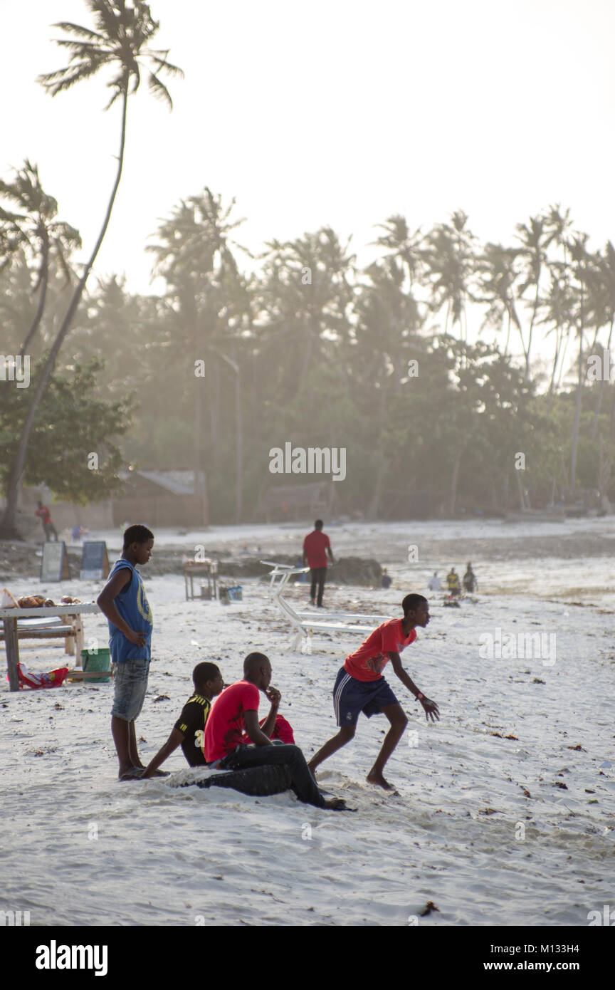 Local Tanzanian youths relaxing on the beach in Nungwi, Zanzibar, playing football in the setting sun with dhow - Stock Image