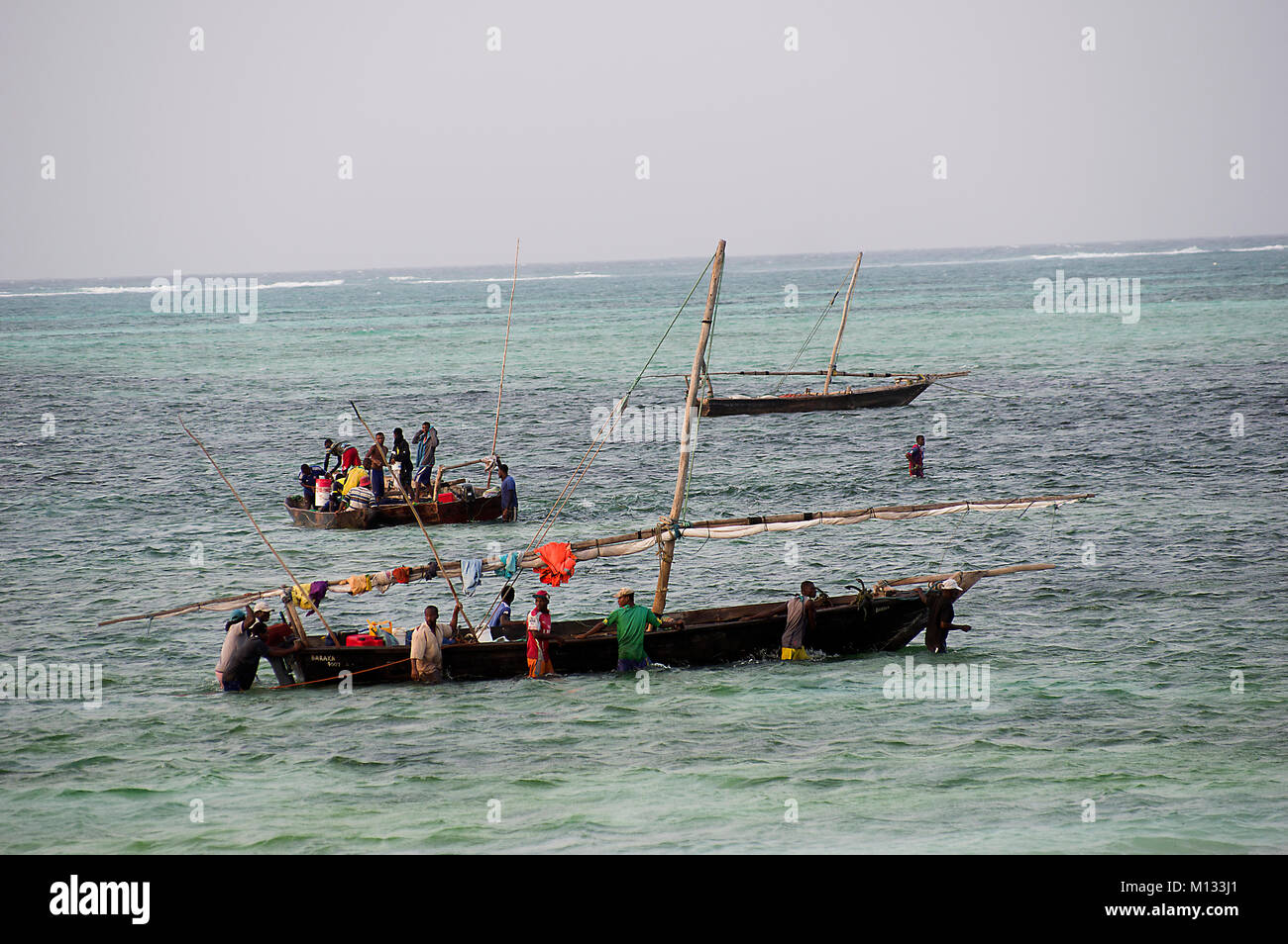 Fishermen going out to sea in traditional dhow boats in Nungwi on the island of Zanzibar with turquoise waters of - Stock Image