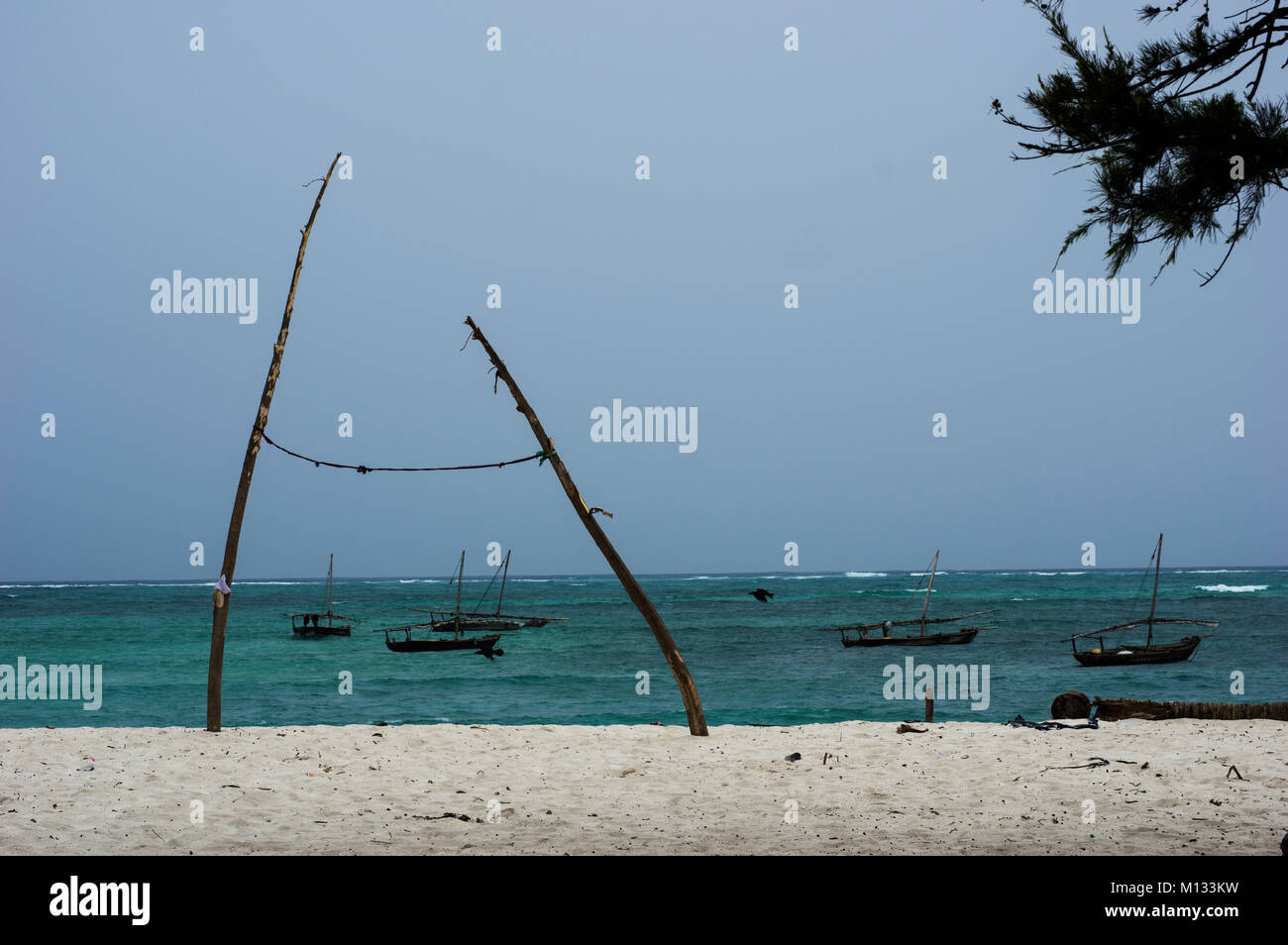 Two poles tied together with string, perhaps an inpromptu washing line, with traditional dhow boats in the background - Stock Image