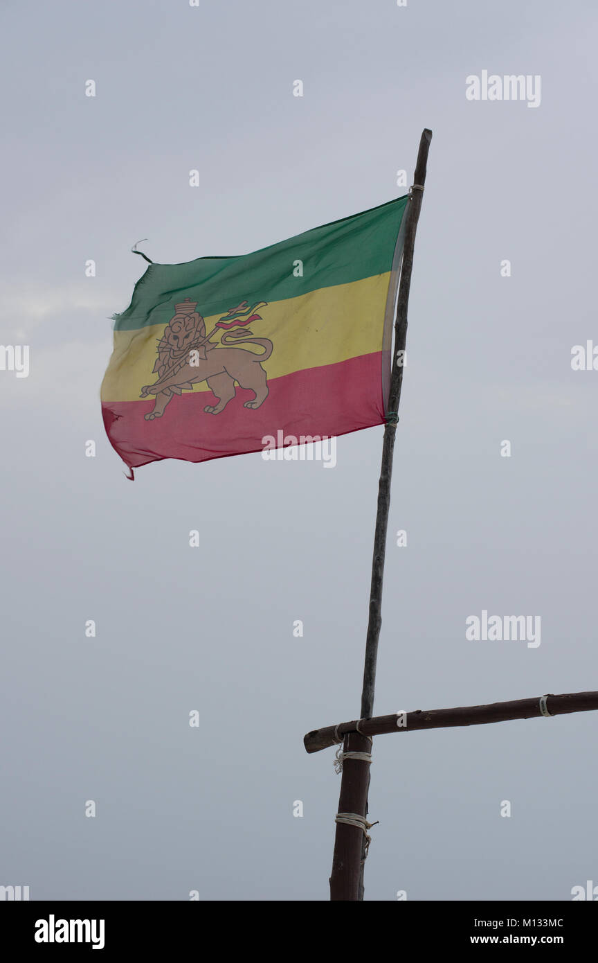 Slightly torn Ethiopian Lion of Judah flag blowing in the breeze with a blue sky background - Stock Image