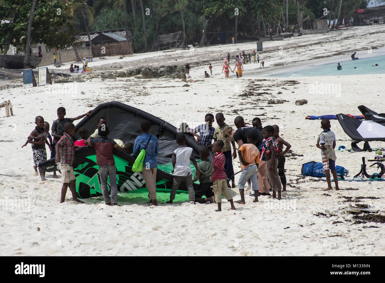mobs of local Swahili children descend upon a kite surfer on the beach in Nungwi, Zanzibar, Tanzania, as he sets - Stock Image