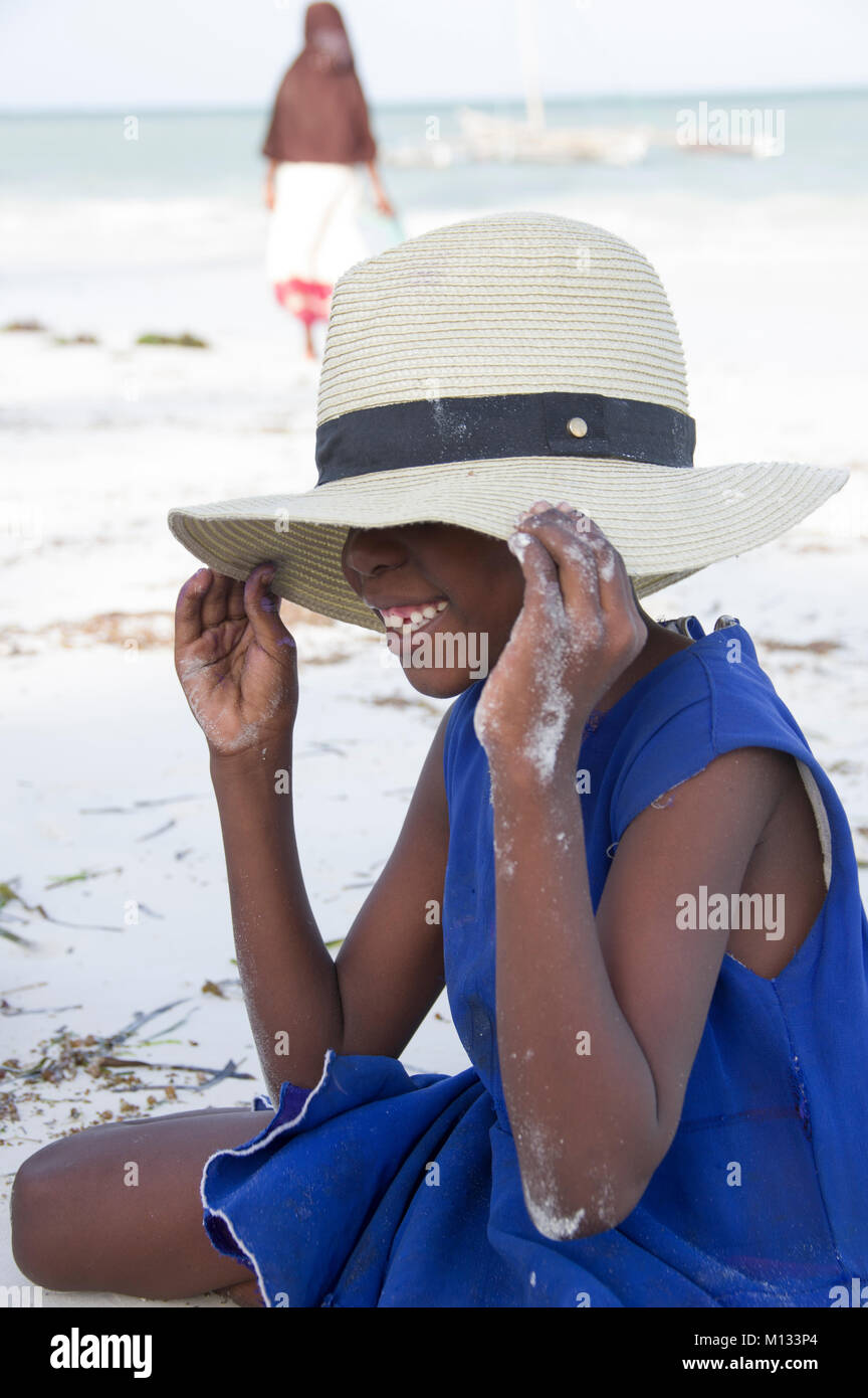 Young African girl in a straw hat her face not visible but smile is visible on a beach with white sand in bright - Stock Image