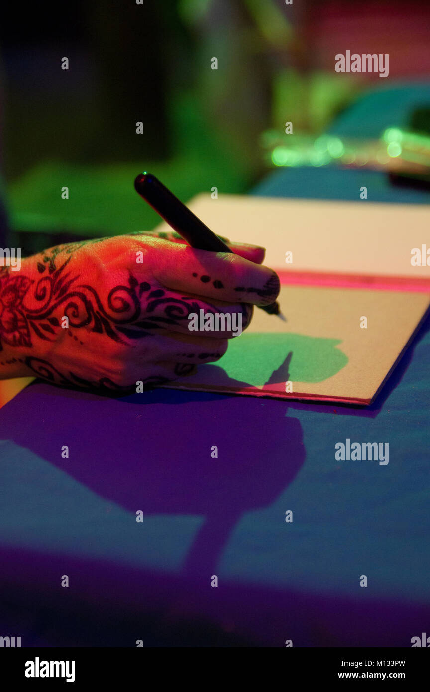 A woman's henna hand is poised to write on a blank piece of notebook paper  with green and red shadows on the - Stock Image