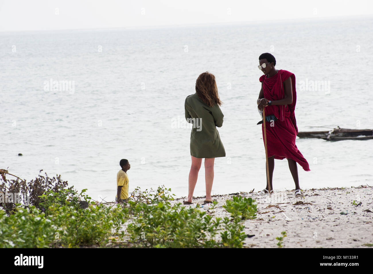 Massi man in traditional red cloak chats with a European woman on the beach in Jambiani Zanzibar Tanzania with a - Stock Image
