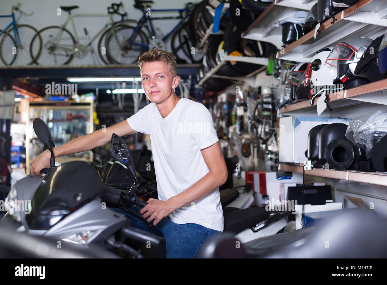 Young man purchaser sitting on the chosen bike in the shop - Stock Image