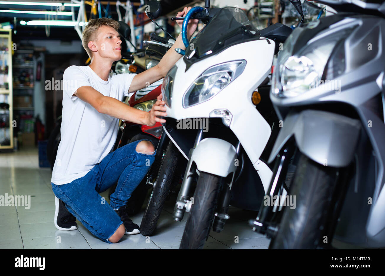 Portrait of cheerful positive man purchaser choosing motorbike in the store - Stock Image