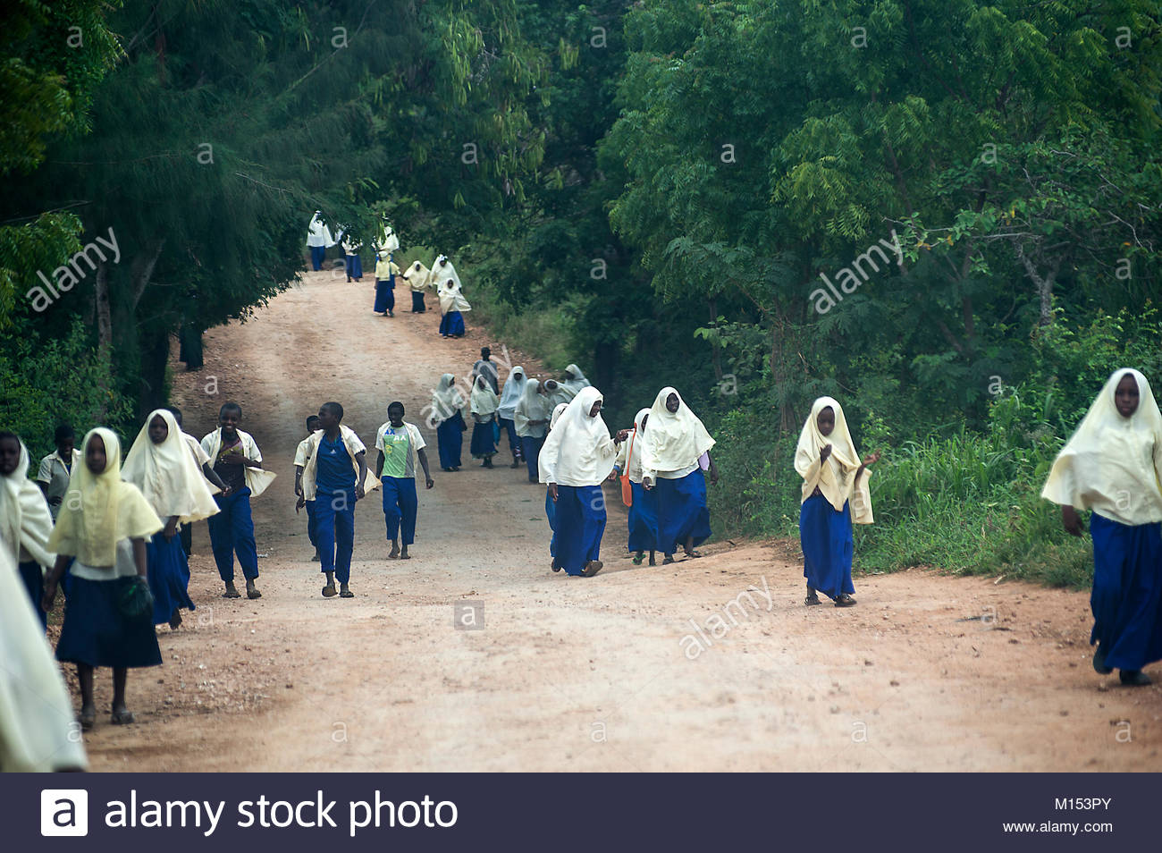 Muslim girls leaving school wearing white and yellow headscarves and blue dresses or robes walking on an unpaved - Stock Image