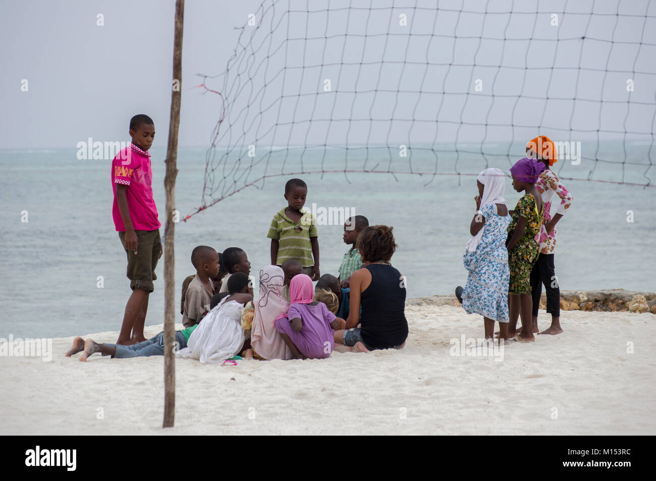 Local children in Zanzibar having a discussion on the white sandy beach in Nungwi, barefoot and wearing colourful - Stock Image