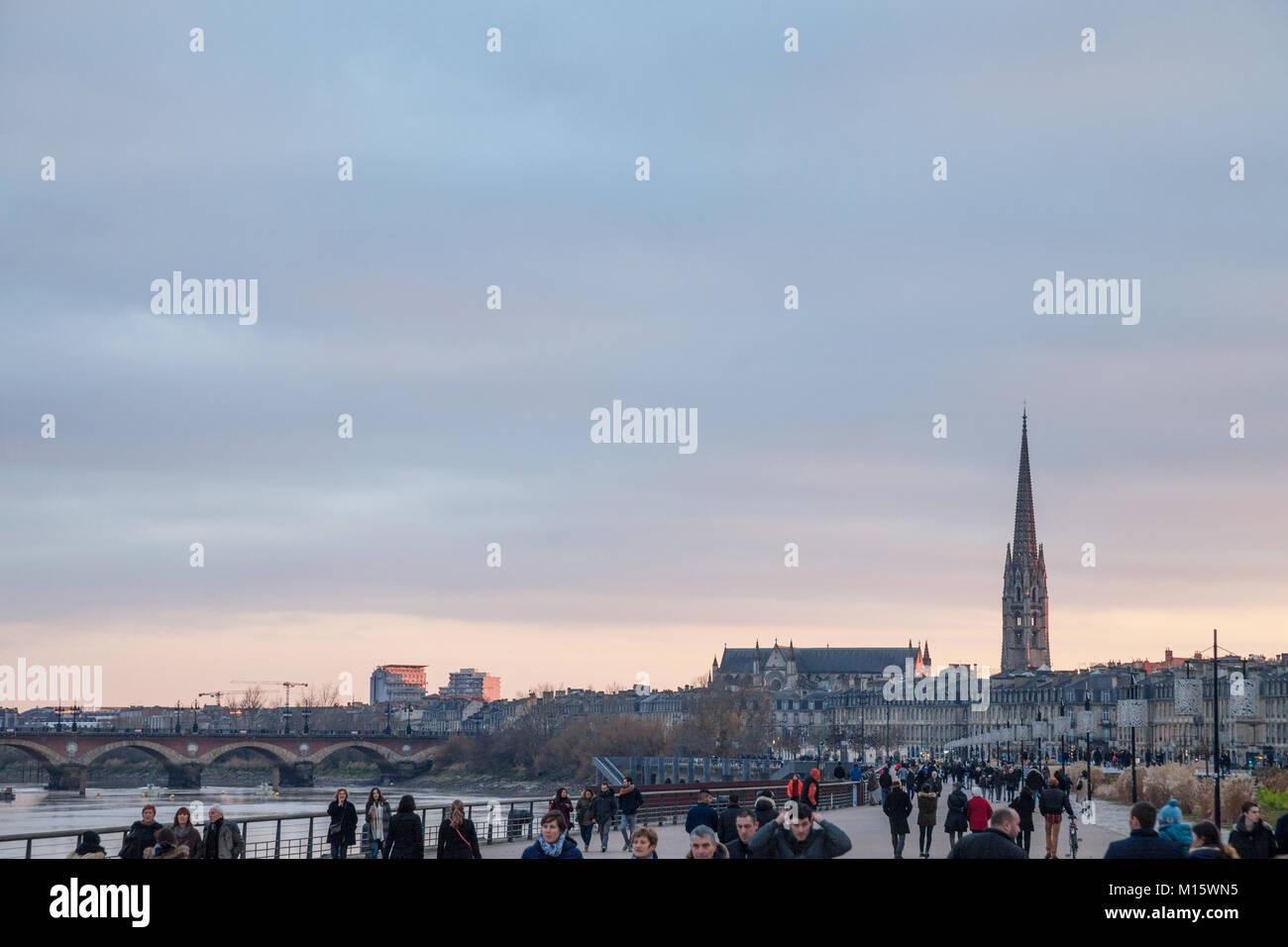 BORDEAUX, FRANCE - DECEMBER 24, 2017: Garonne Quays (Quais de la Garonne) at dusk with a crowd passing by. Saint - Stock Image