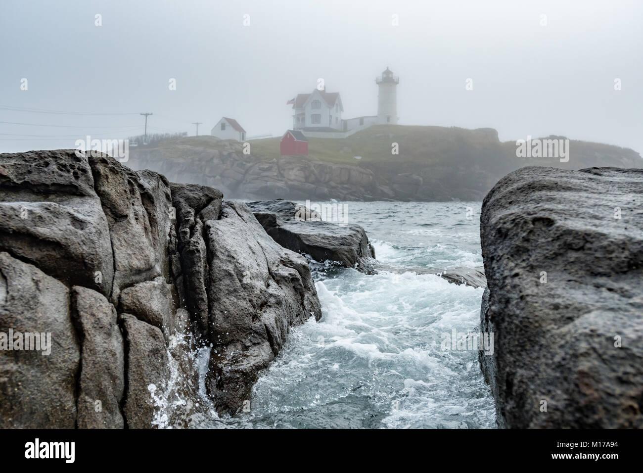 Water Rushes Through Rocks at Cape Neddick Lighthouse along Maine's coast - Stock Image