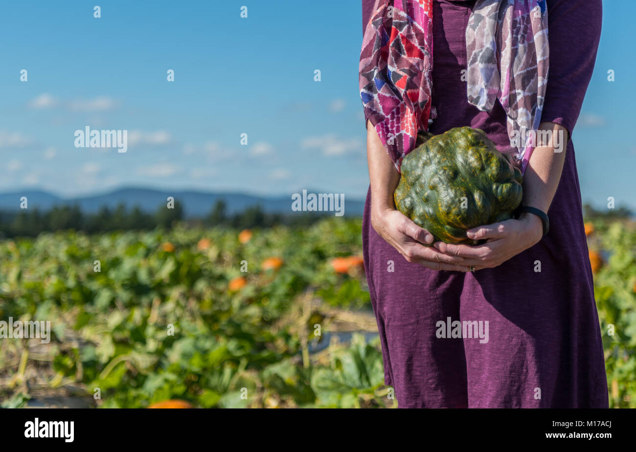 Woman Holding Bumpy Pumpkin with Copy Space to left - Stock Image