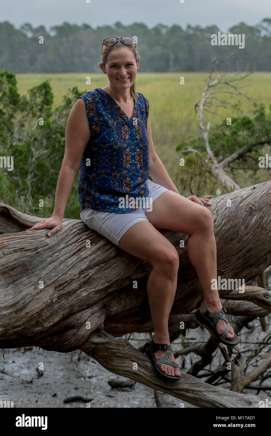 Woman Sits on Large Tree trunk in front of grassy marsh - Stock Image