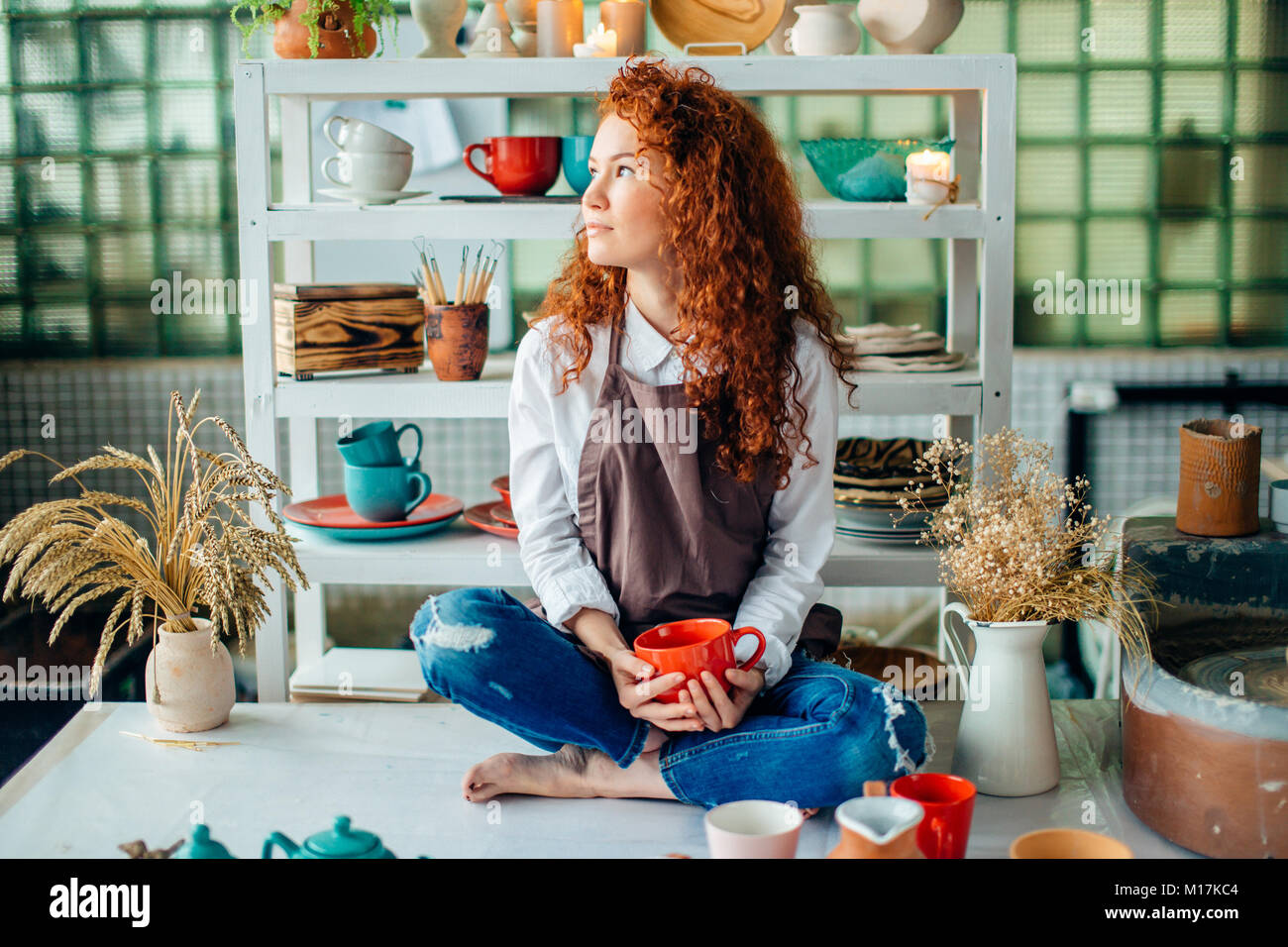 redhead woman sitting in lotus pose in clay shop - Stock Image