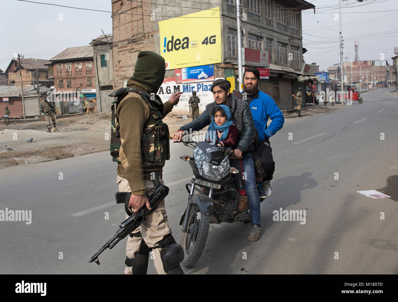 Srinagar, Indian-controlled Kashmir. 28th Jan, 2018. An Indian paramilitary trooper stops a motorcyclist during - Stock Image