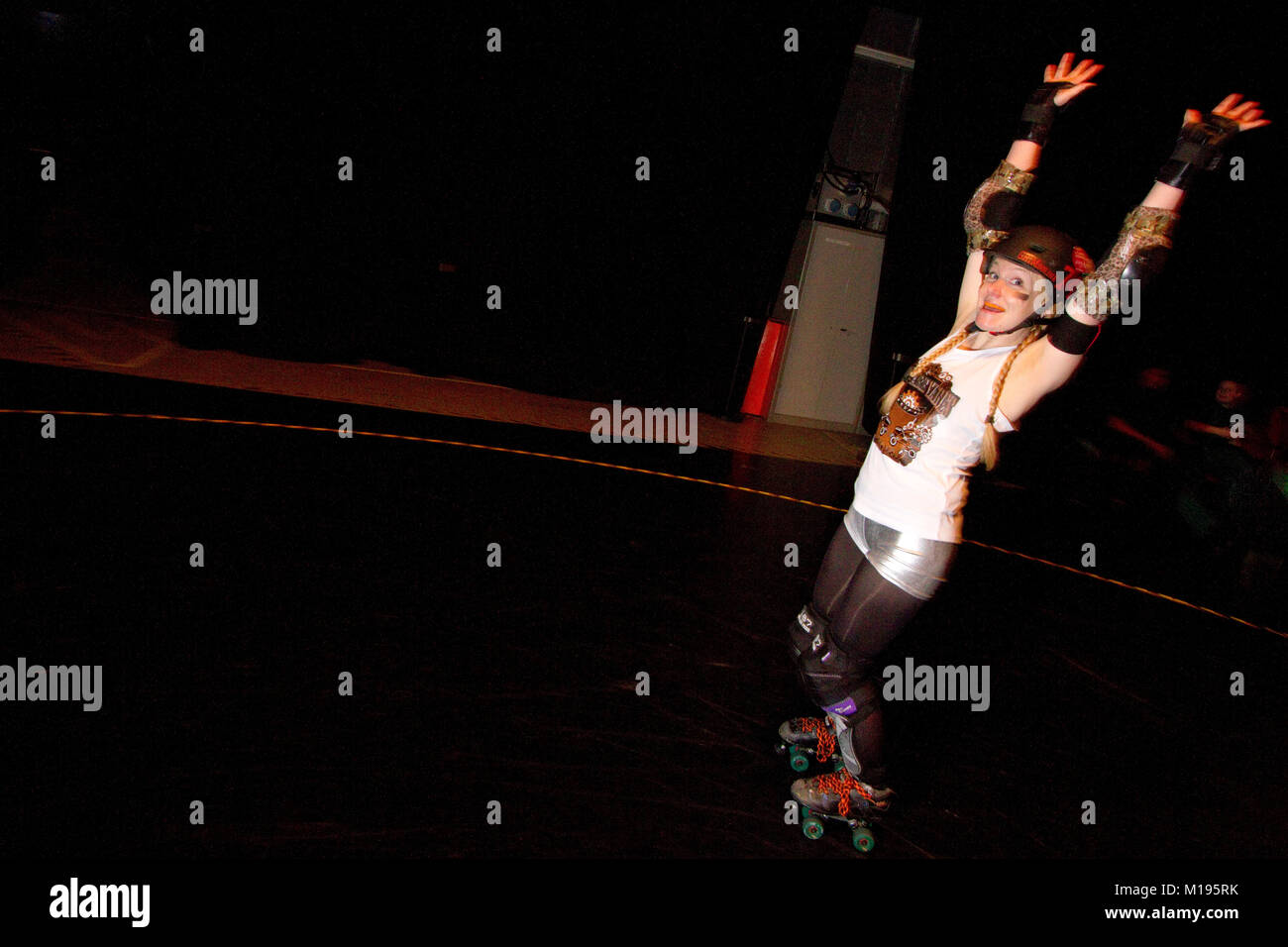 Roller derby skater warming up looks at the camera - Stock Image