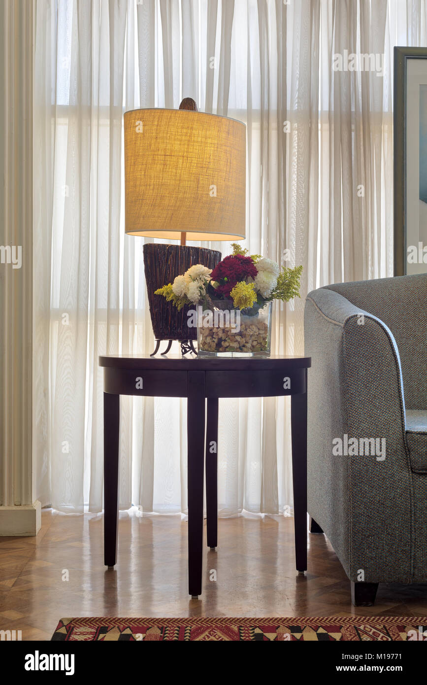 Interior shot of illuminated table lamp and colorful flowers planter on small dark brown wooden table on background - Stock Image