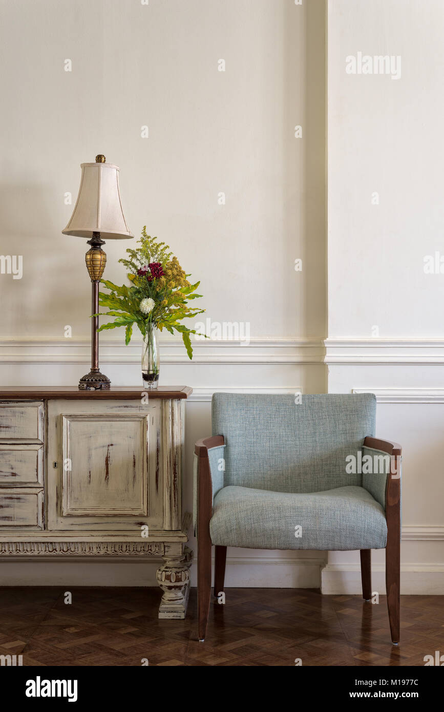 Interior shot of light blue armchair and cream vintage sidebar with table lamp and flowers planter on off white - Stock Image