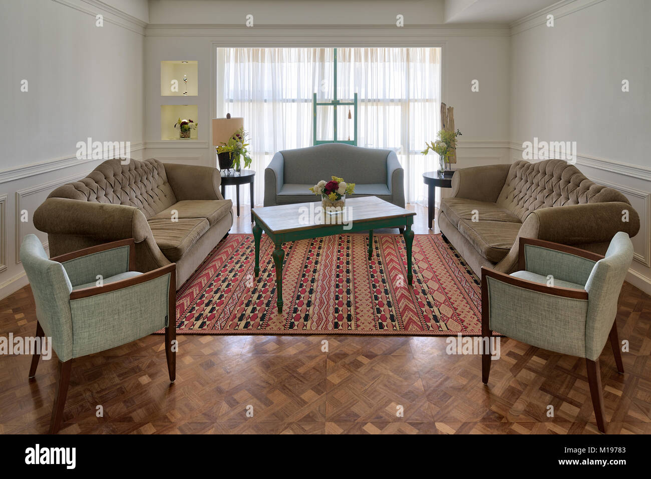 Interior shot of luxury modern living room with three couches, two armchairs, and vintage wooden table on background - Stock Image