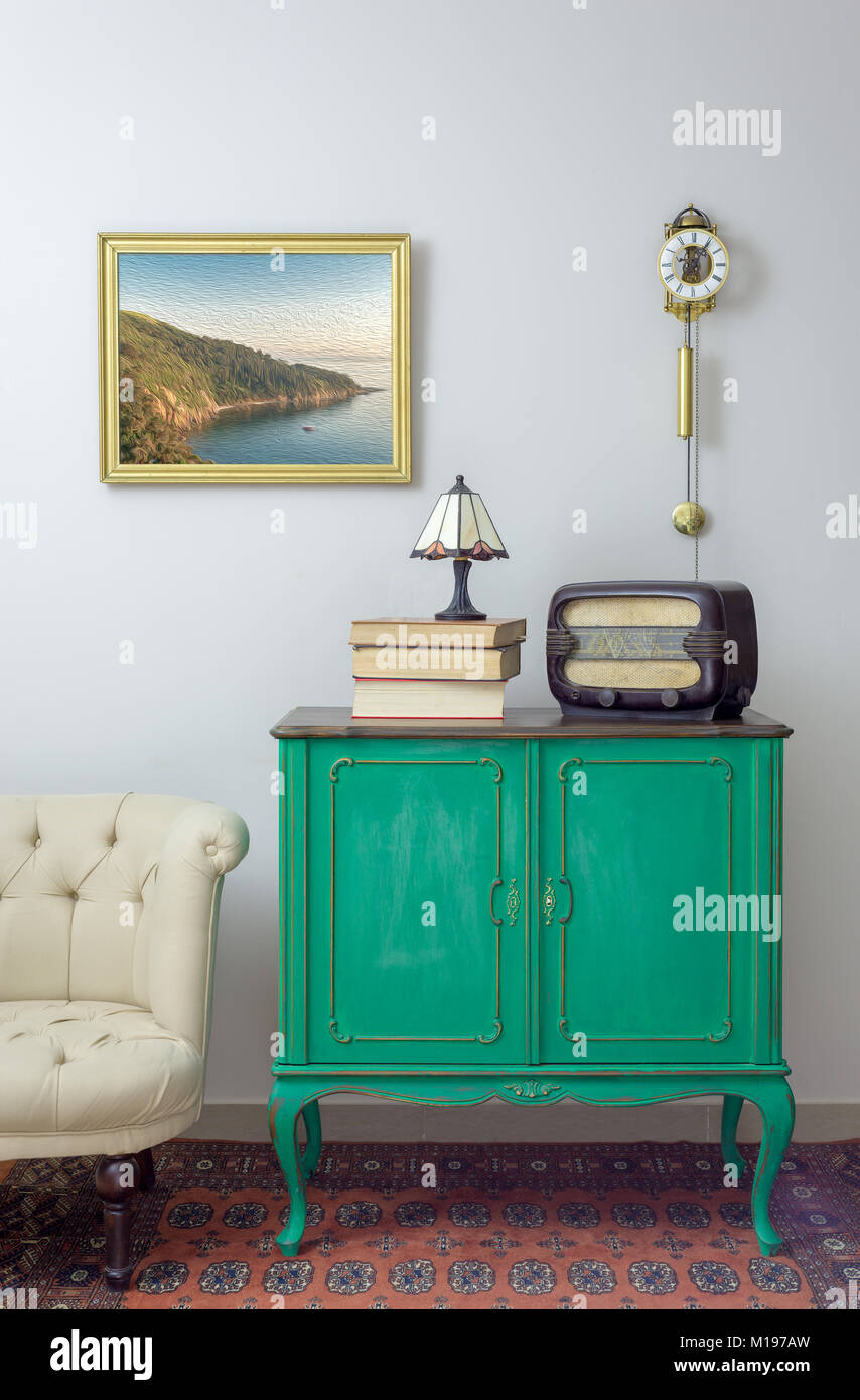 Interior shot of green vintage sideboard with old radio, stack of old books, and table lamp on background of off - Stock Image