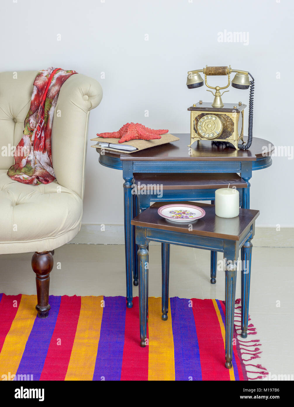 Interior shot of old golden telephone set, white candle, red starfish and colorful ornate plate over three nested - Stock Image