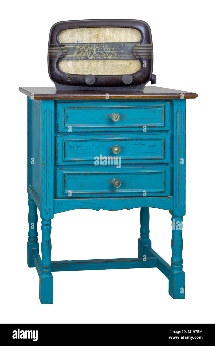 Vintage Furniture - Turquoise commode (Chest of Drawers) with 3 drawers with brass fittings and aged analog radio - Stock Image
