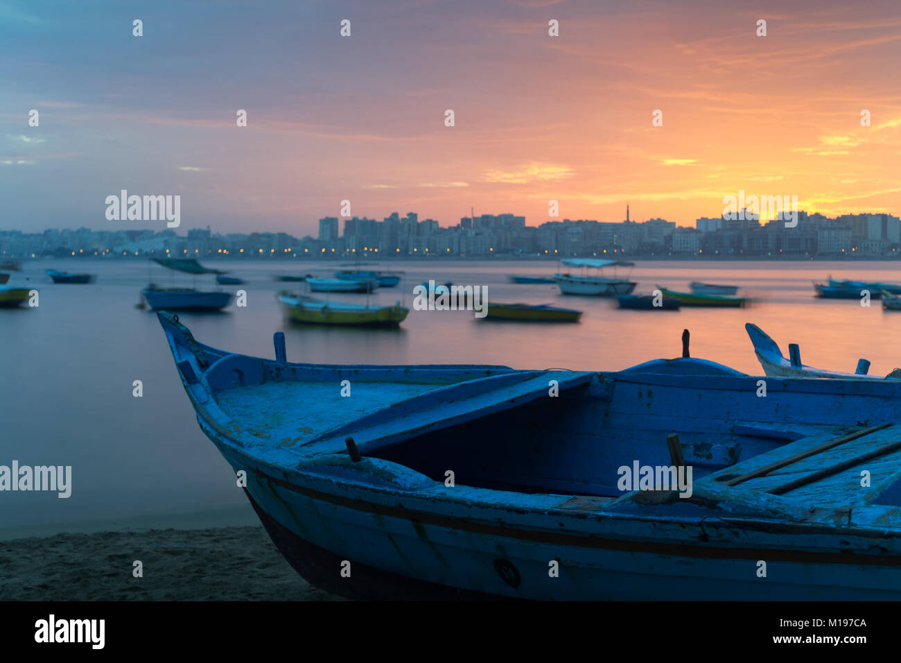 Turquoise blue fishing boat on the beach at sunrise with Alexandria skyline in far distance and colorful sky at - Stock Image