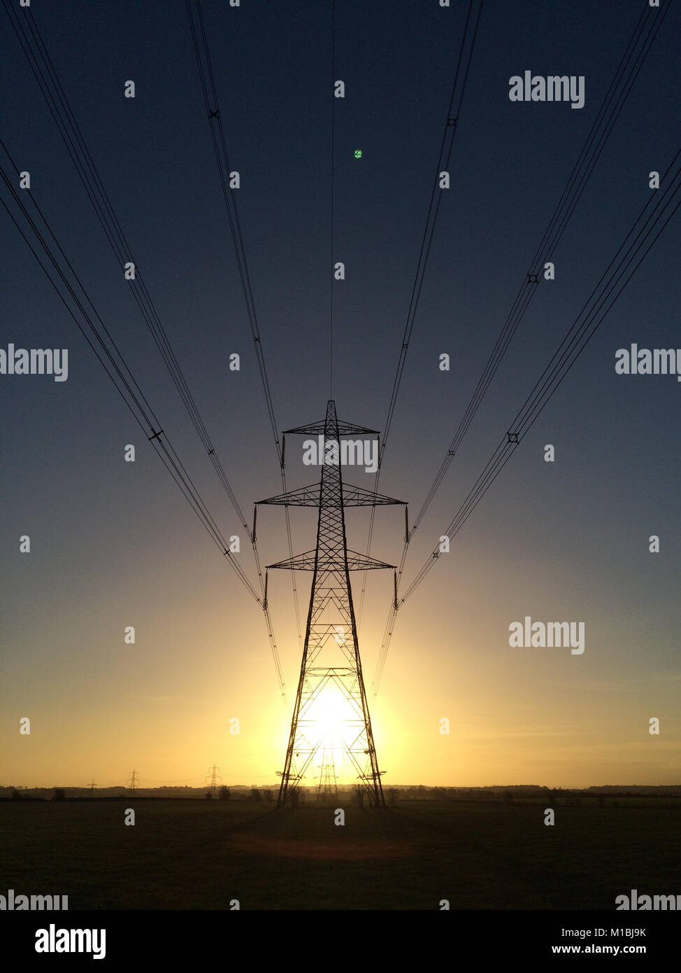 Electricity pylon at sunrise with sun bursting though showing energy and light. - Stock Image