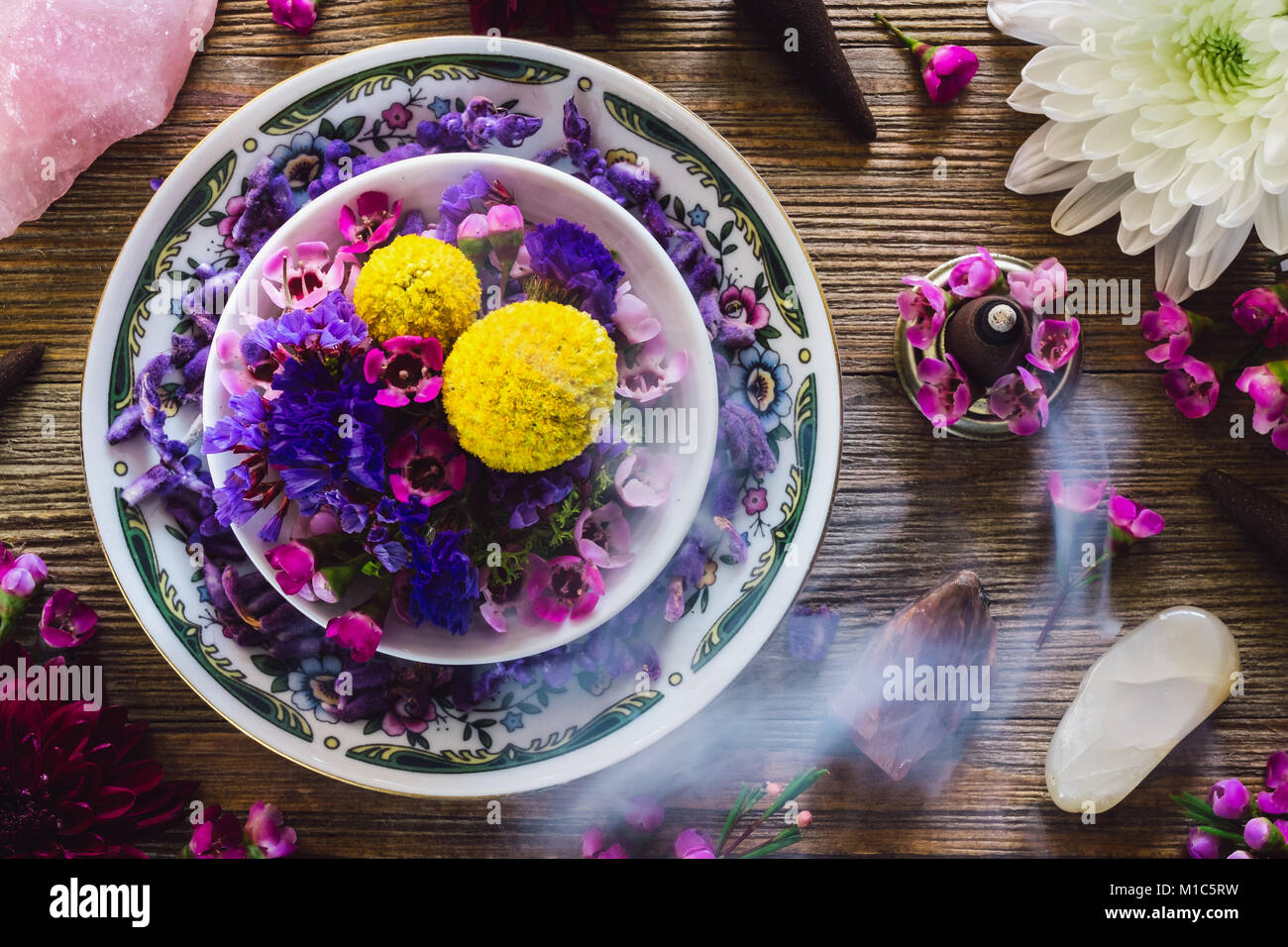 Table with Plate of Flowers, Rose Quartz, Moonstone and Incense. - Stock Image