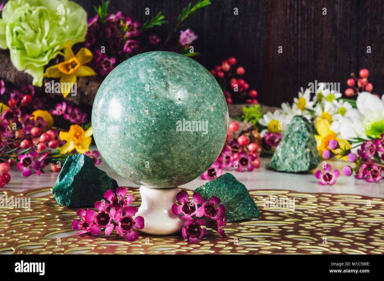 Green Aventurine Sphere Surrounded with Assorted Flowers and Rough Stones - Stock Image