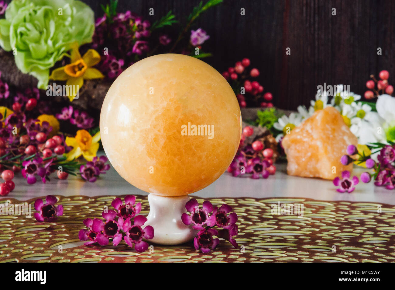 Yellow Aventurine Sphere Surrounded with Assorted Flowers - Stock Image