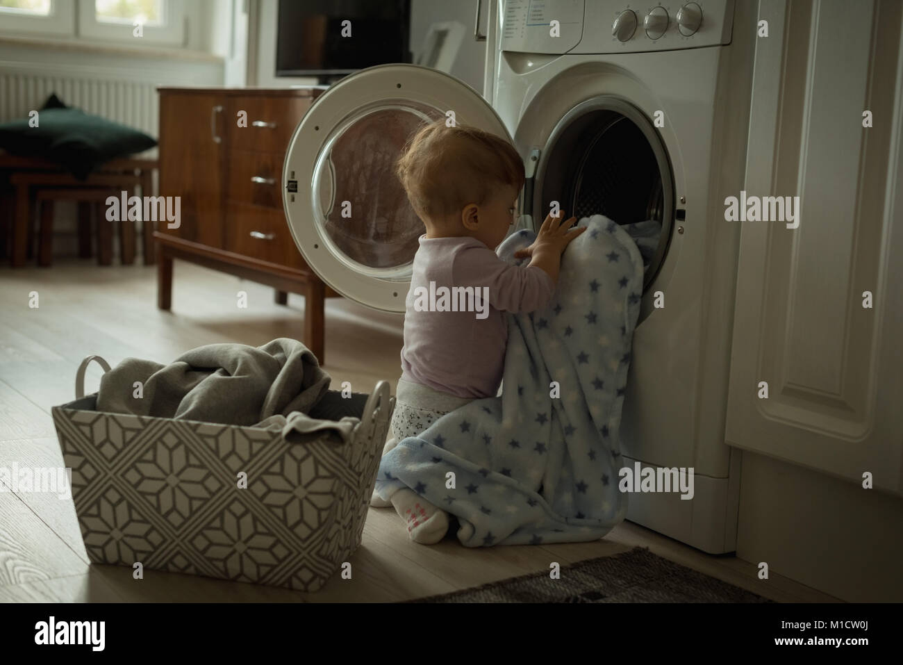 Baby putting clothes inside the washing machine - Stock Image