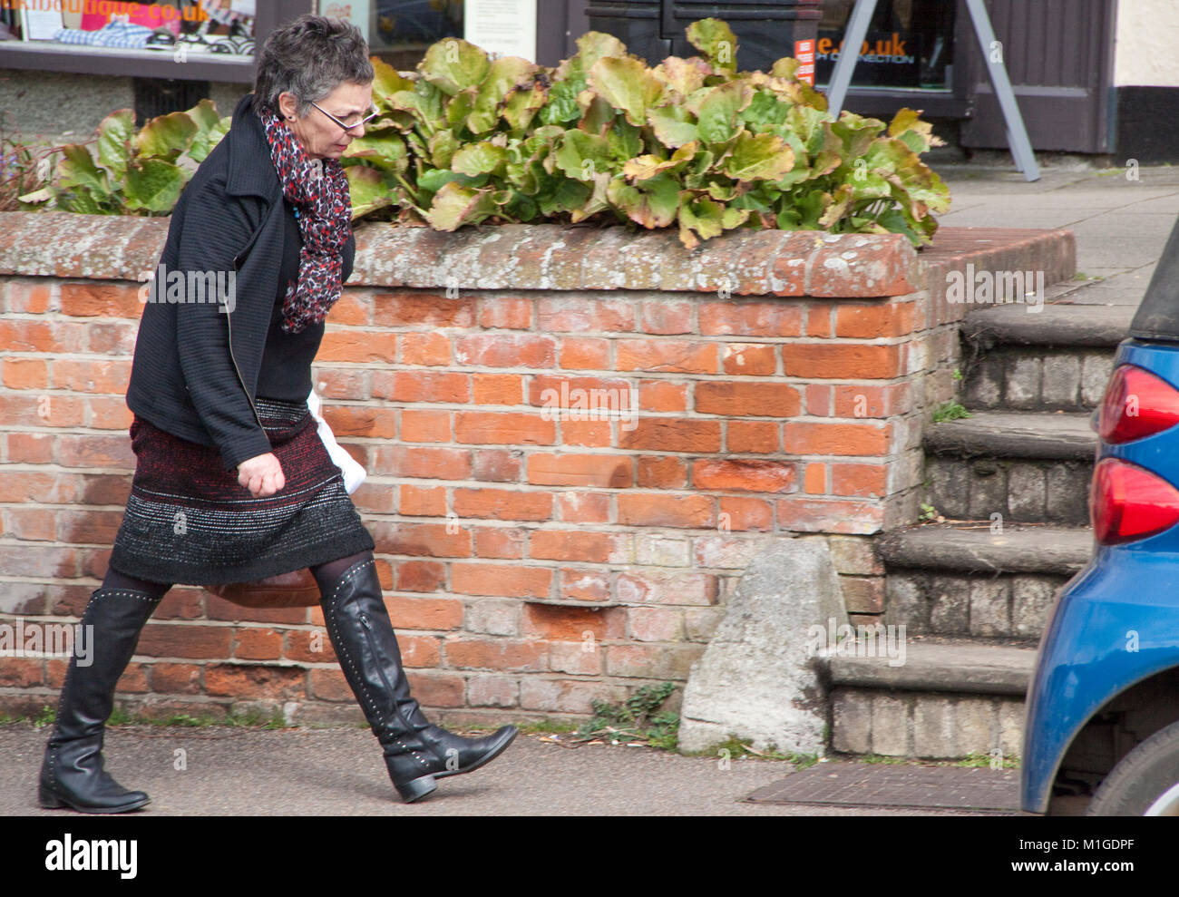 Middle aged lady strides determinedly uphill - Stock Image