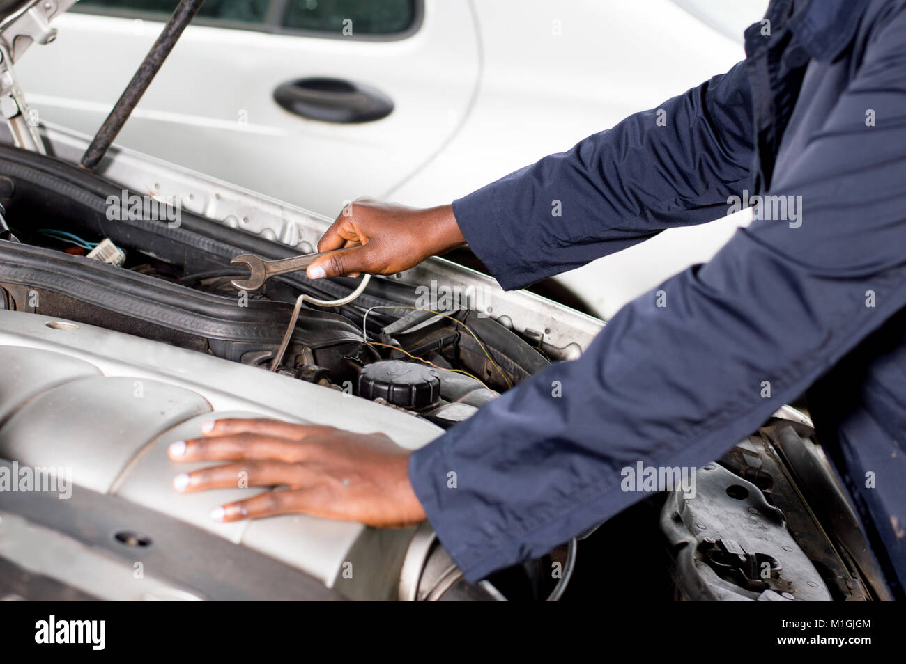 Closeup  of a hand holding a key on the engine of a broken car. - Stock Image