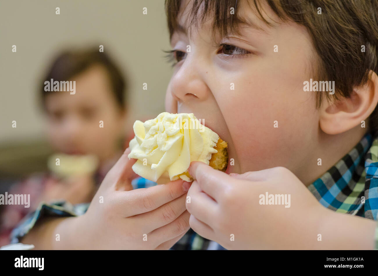 a-close-up-of-a-young-boy-eating-a-cupcake-M1GK1A.jpg