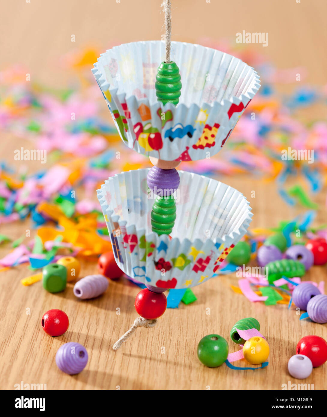 Budgerigar, Budgie (Melopsittacus undulatus). Assembly instruction for budgeriar toy, made from paper muffin liners - Stock Image