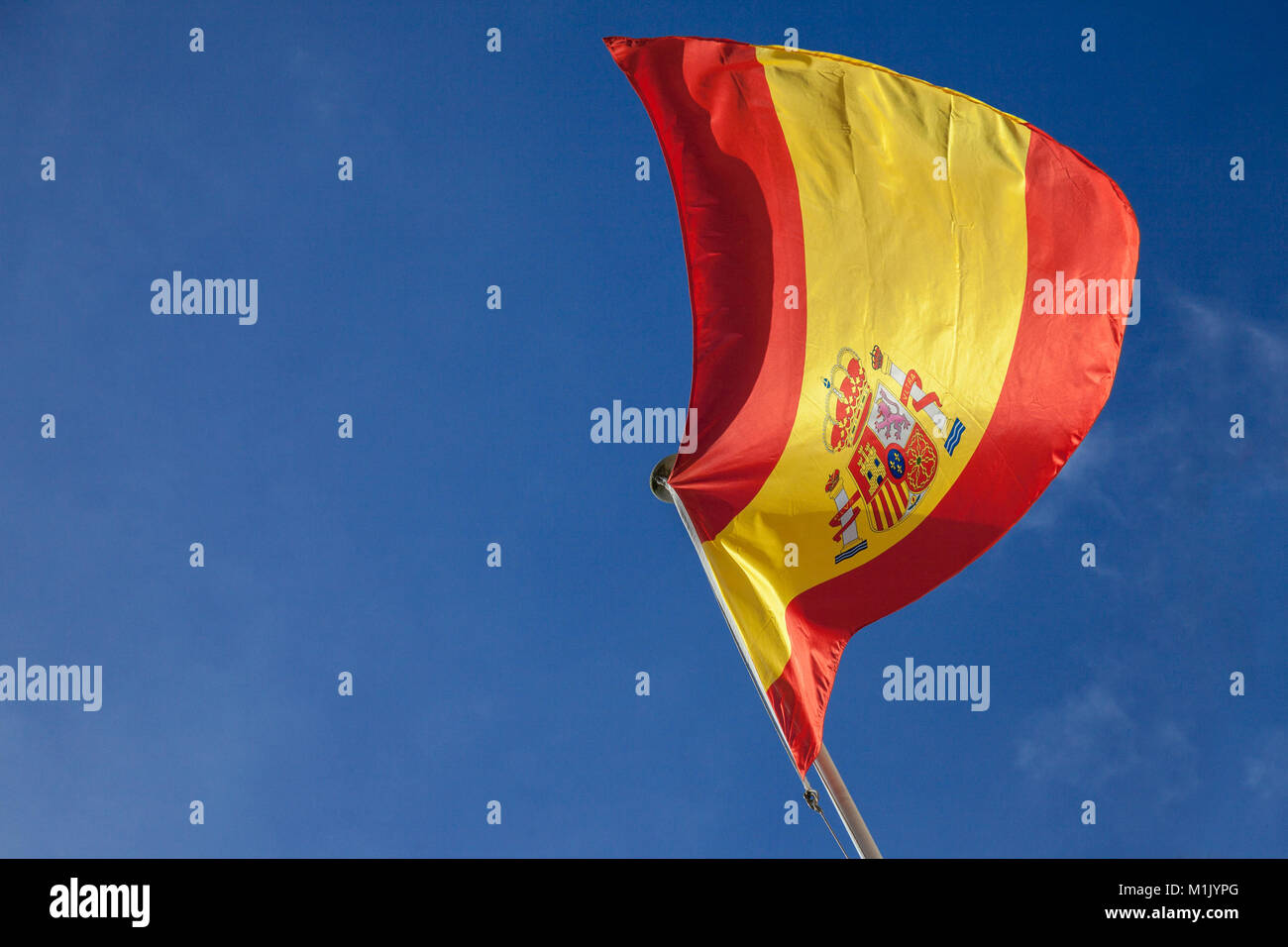 Picture of the Spanish flag waiving in the air on a sunny afternoon with a blue sky background. This flag is the - Stock Image