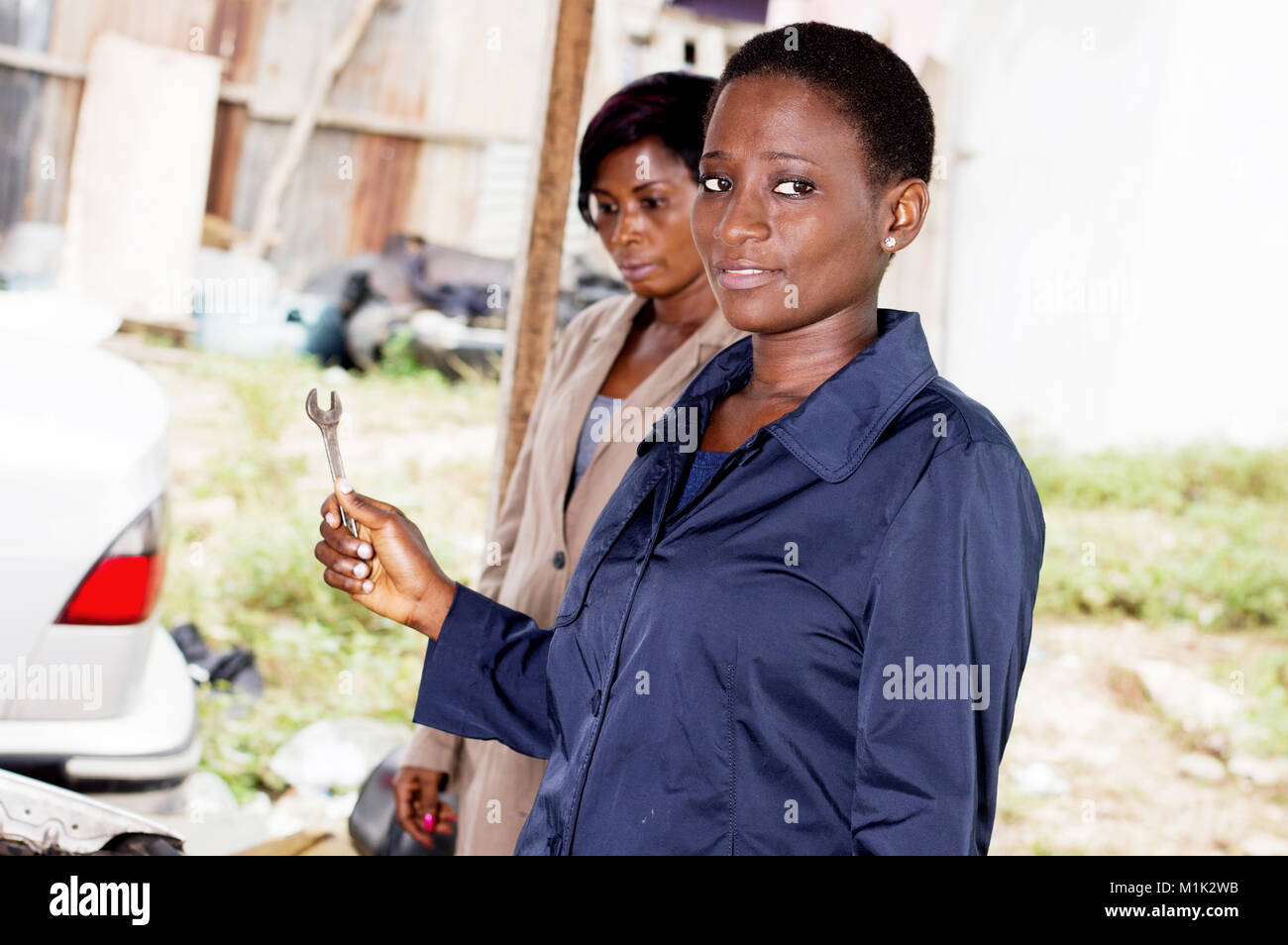 Young woman mechanic holds a key next to the owner of this car. - Stock Image