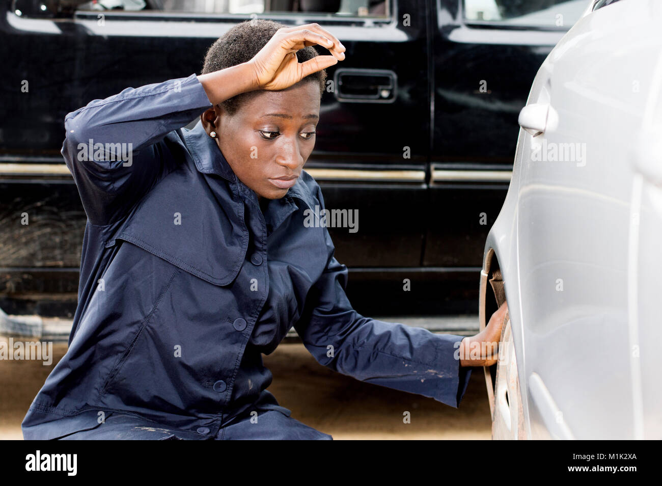 Closeup  of young woman mechanic changing the tire of a car in her garage. - Stock Image