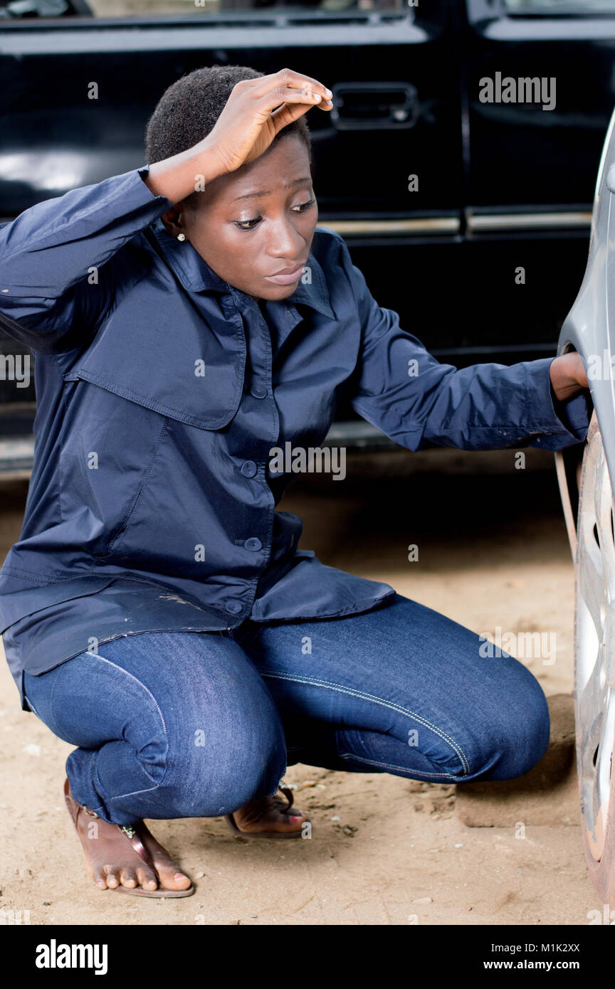 Young female mechanic ready to remove the tire from this car. - Stock Image