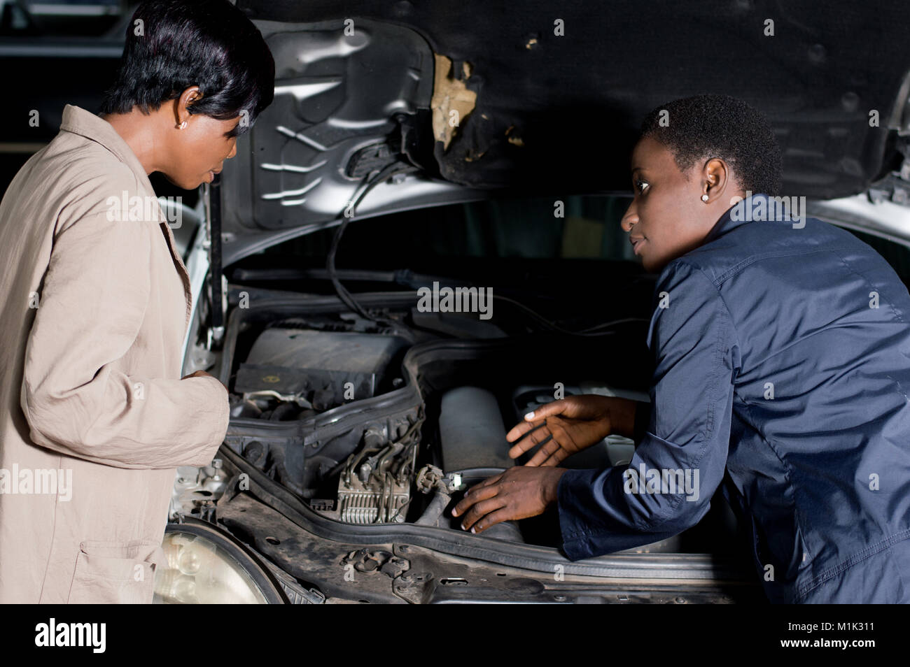 The mechanic explains the breakdown of the car to its owner at the workshop. - Stock Image