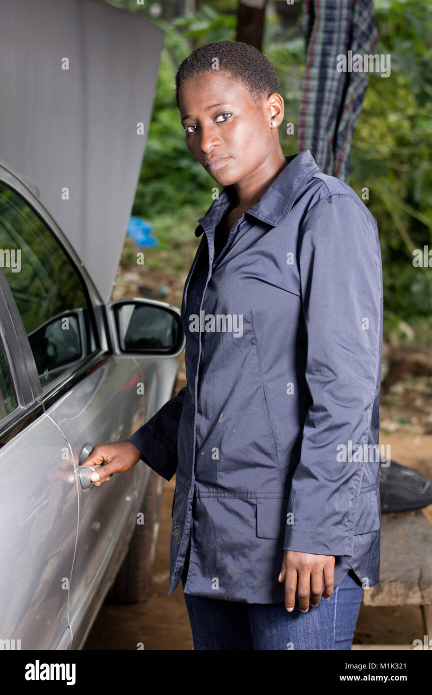 Young mechanic opening the door of a car in the garage and looking at the camera - Stock Image