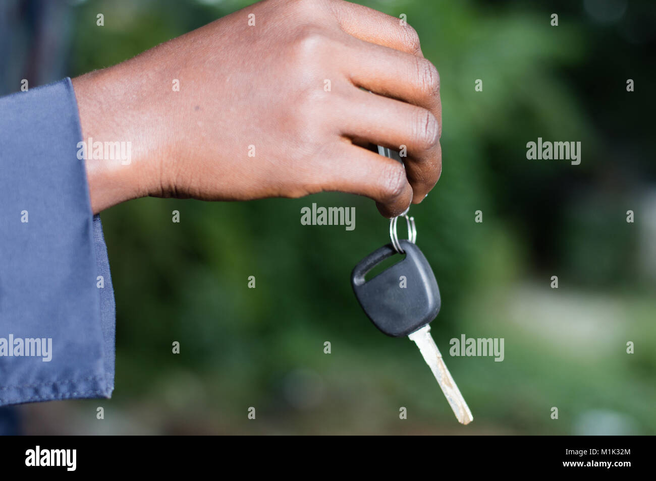 a hand holding a car ignition key outside. - Stock Image