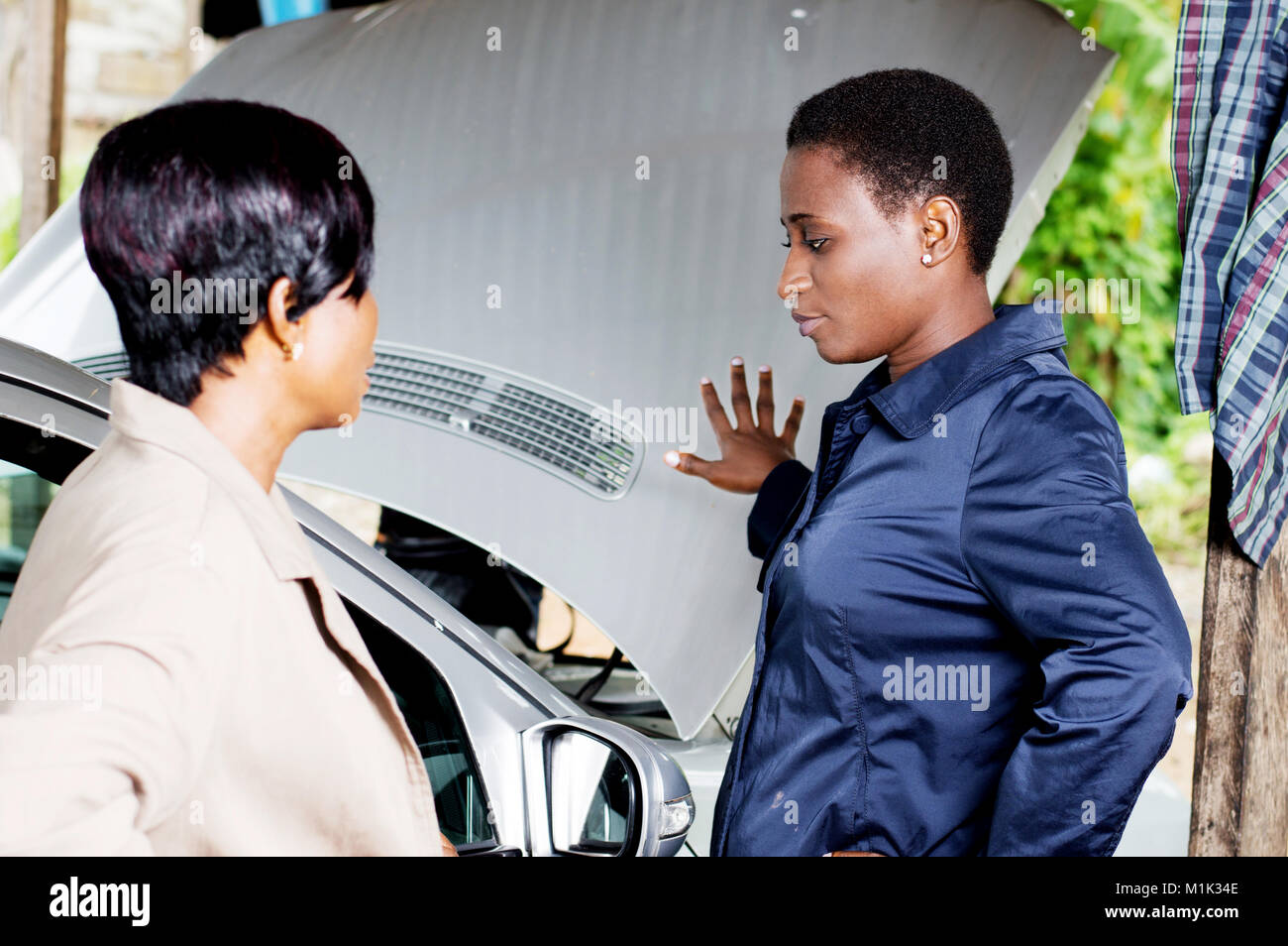 Young woman explains the breakdown of her car to a mechanic. - Stock Image
