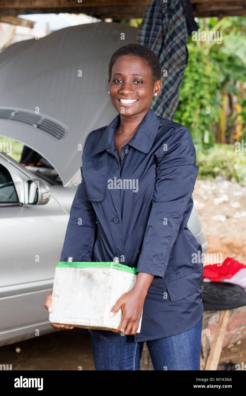 Young female mechanic raises a car battery to place it in the engine of this car. - Stock Image