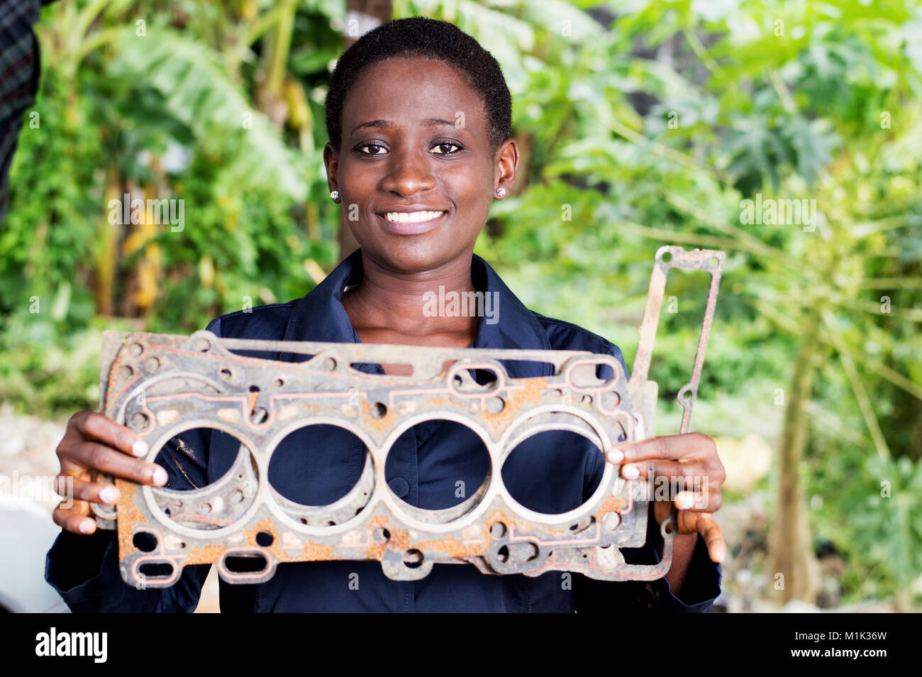 Young woman mechanic holds a damaged car part in her workshop. - Stock Image