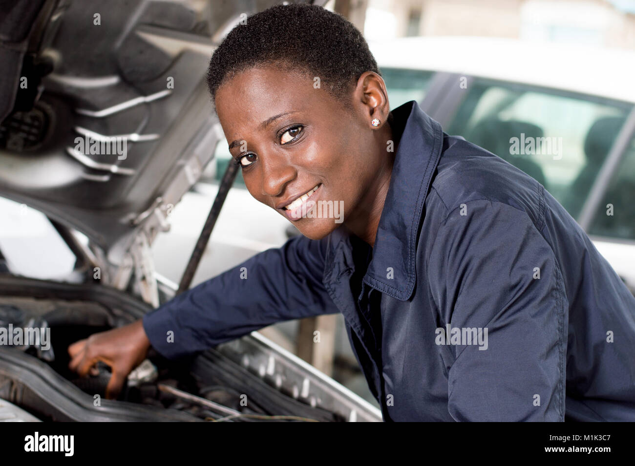 Young female mechanic repairs a car by putting the engine in good condition. - Stock Image